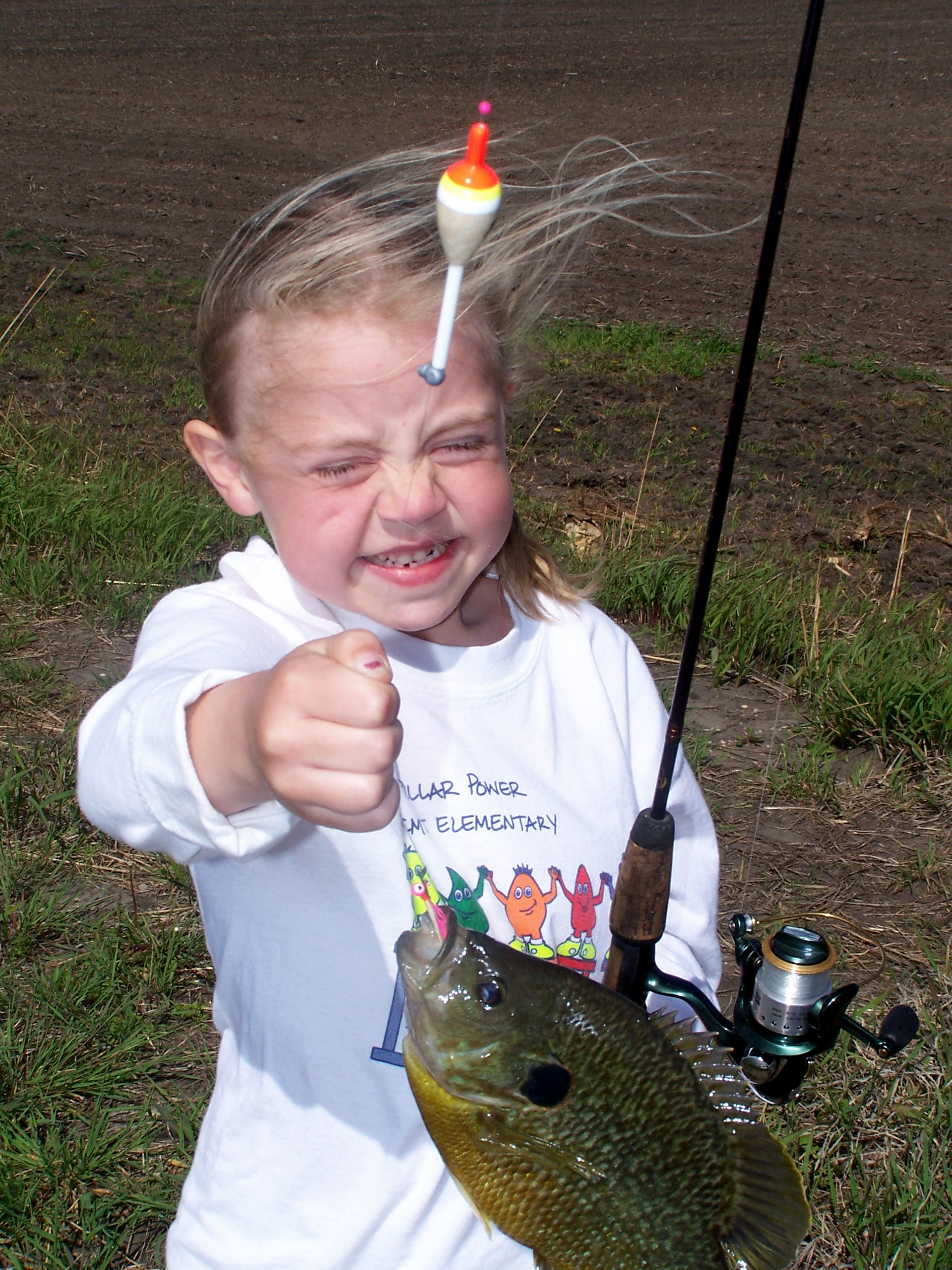 Young Makenna Amsbaugh holding up the bluegill fish she just caught.